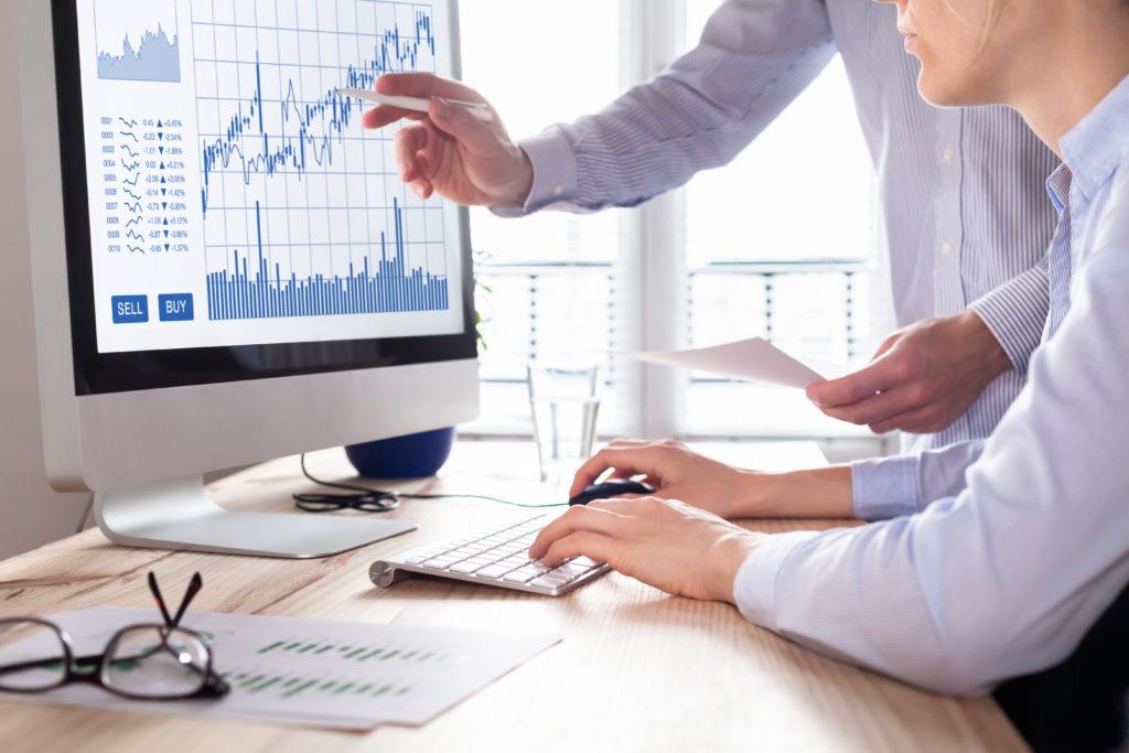 Team av forretningsansatte som arbeider med valuta/trading diagrammer og grafer på dataskjerm, konsept om aksjemarked, investering, finans, salg og kjøp.