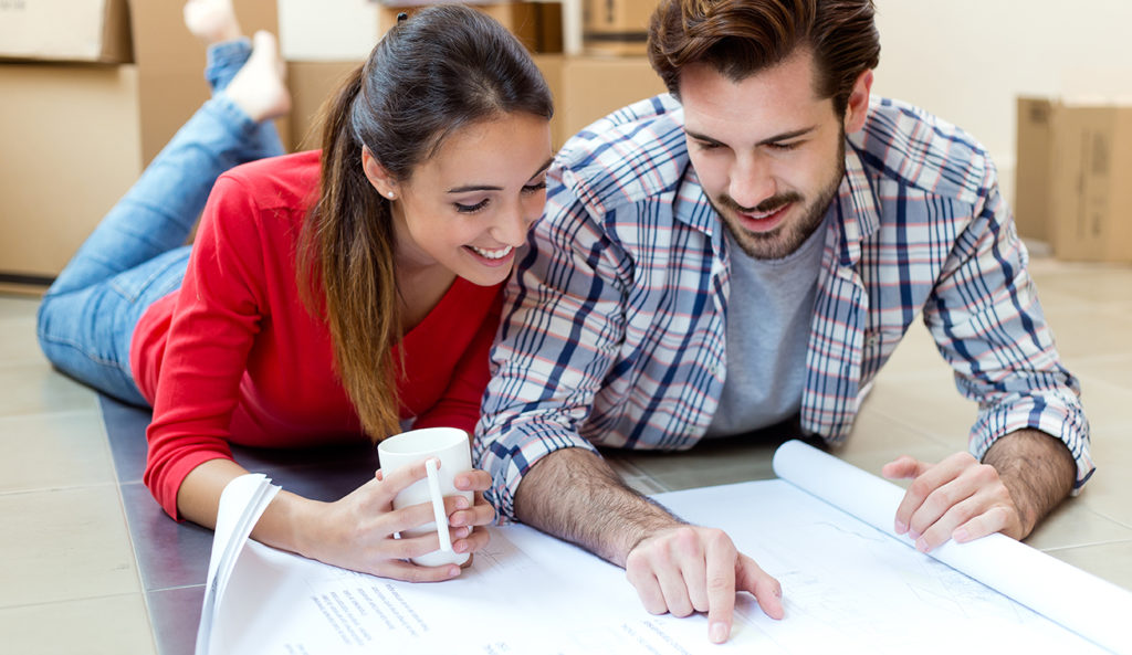 Ungt par på gulv studerer hustegninger